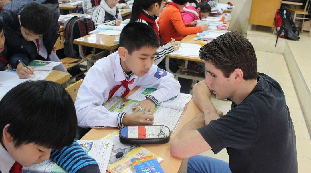 A volunteer helps his students in class during his teaching work experience in Vitenam